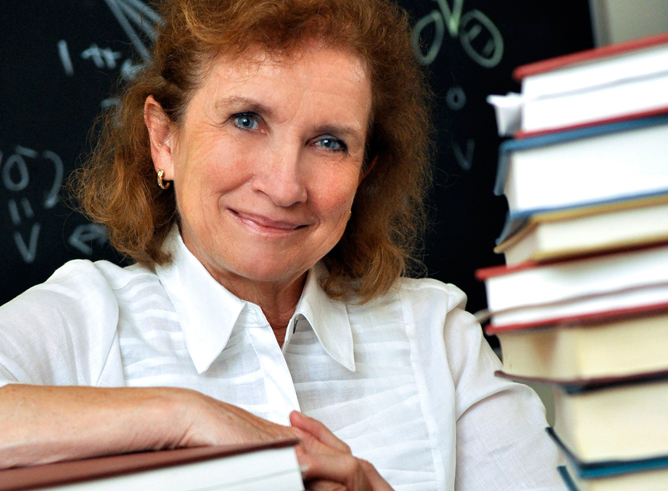 Dr. Marcetta Darensbourg rests her arm on a stack of books in her office
