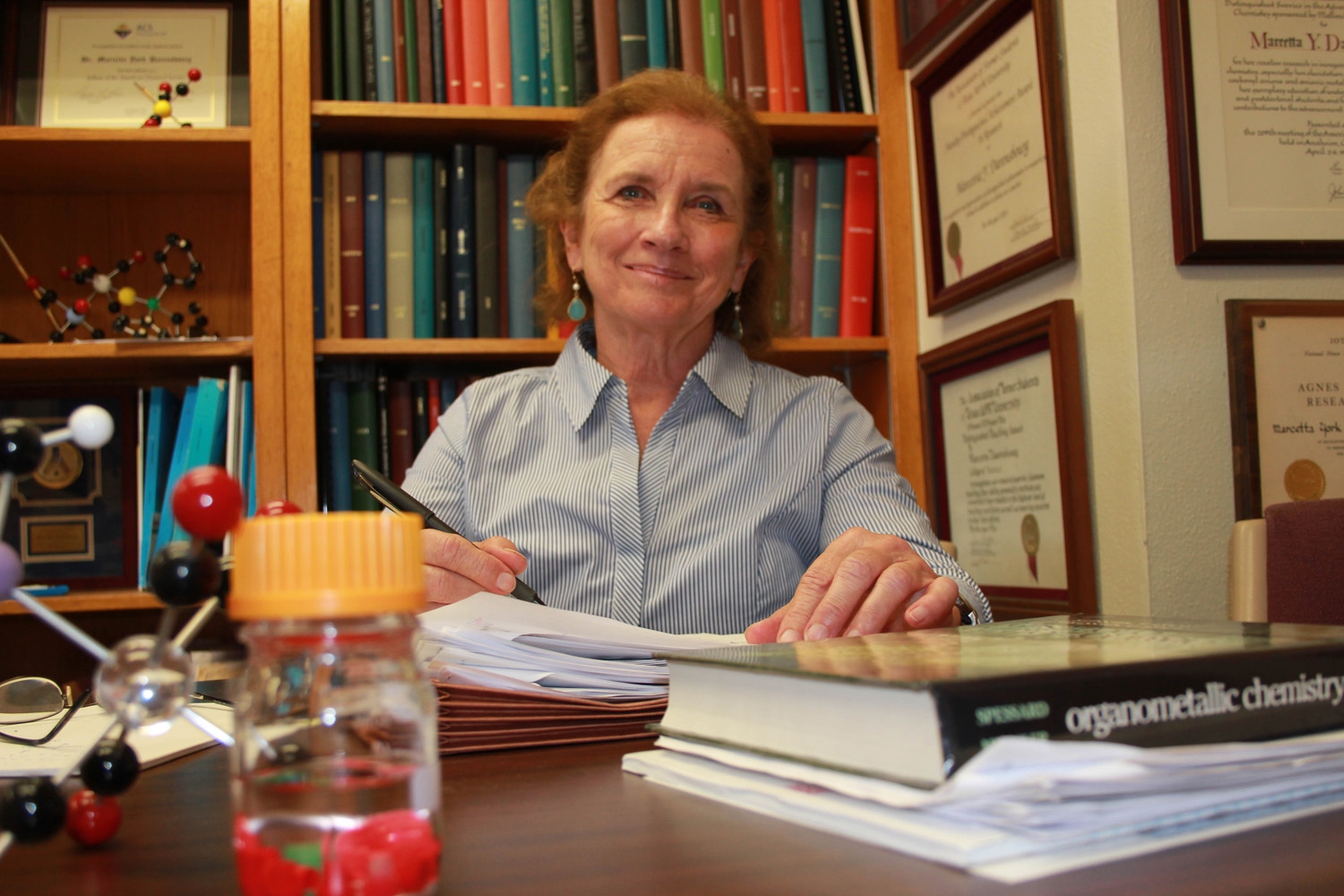Dr. Marcetta Darensbourg smiles at her desk surrounded by papers, books and chemistry models