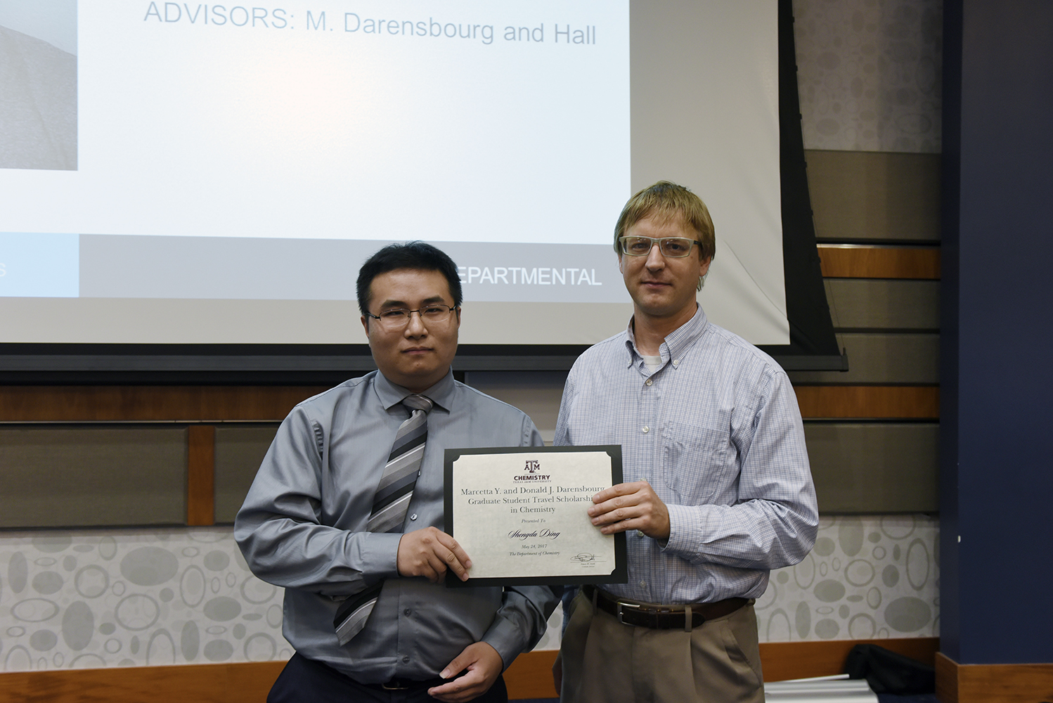 A chemistry graduate student receives an award from a chemistry professor