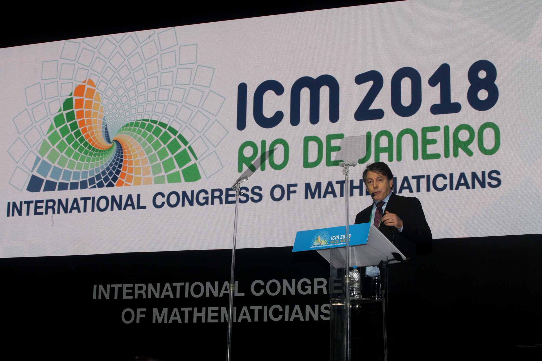 A science faculty member speaks at a podium at the International Congress of Mathematicians