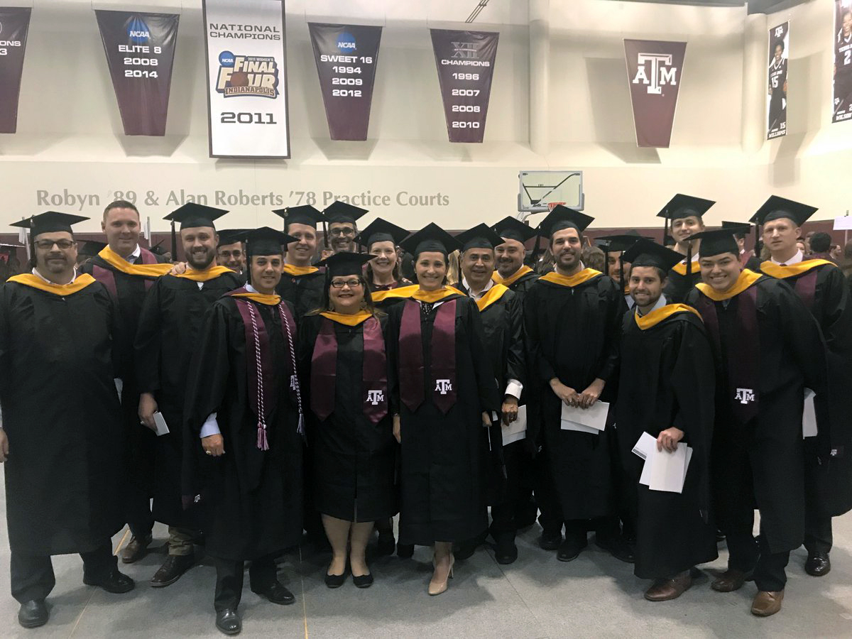 Group of science graduates in their cap and gown and A&M regalia at Texas A&M graduation