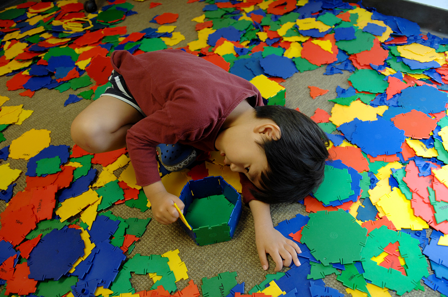 An elementary student sits and builds a tower on the floor with colorful tiles strewn around him