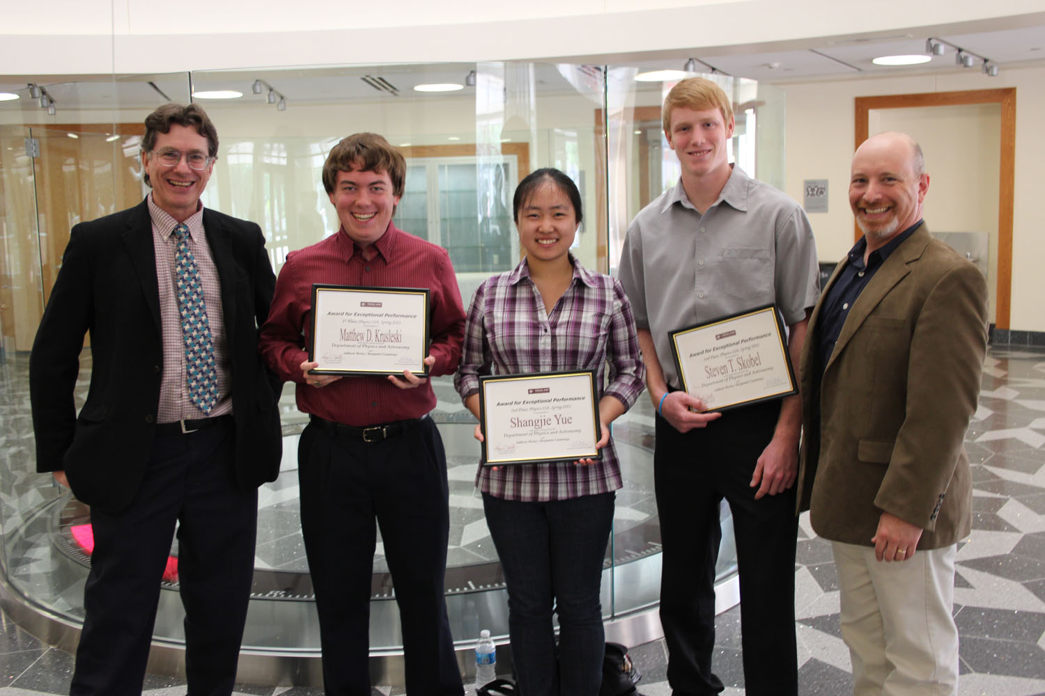 Three science students hold framed awards alongside two physics professors