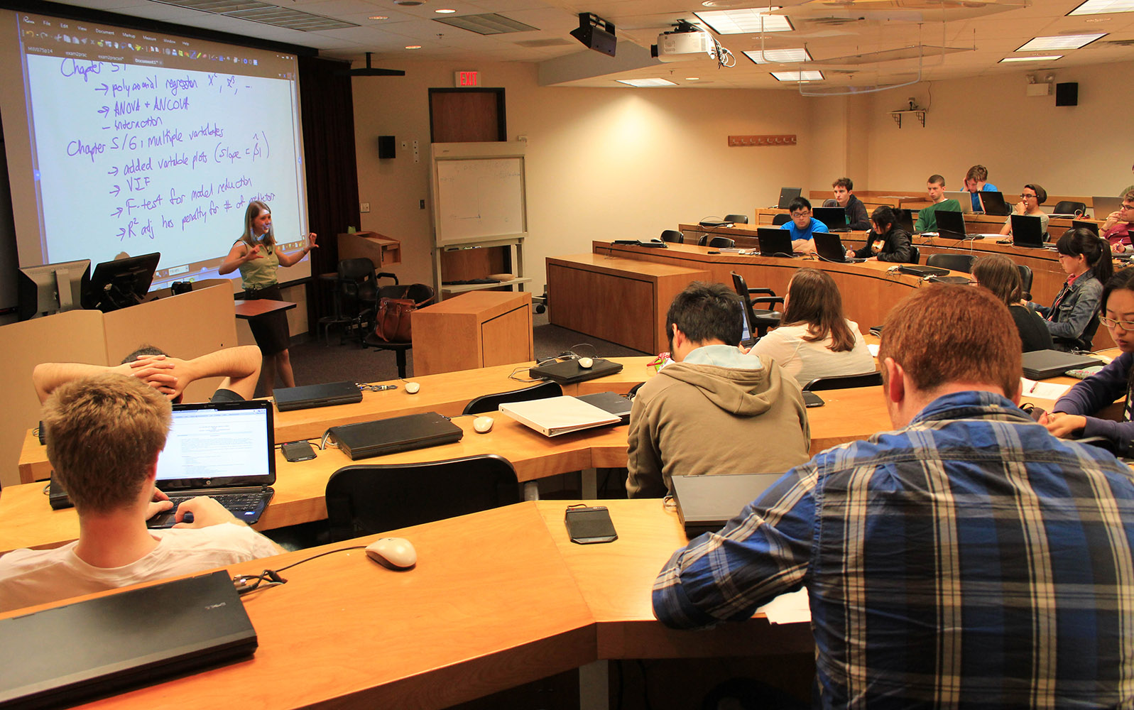 A statistics instructor teaches to a room full of students