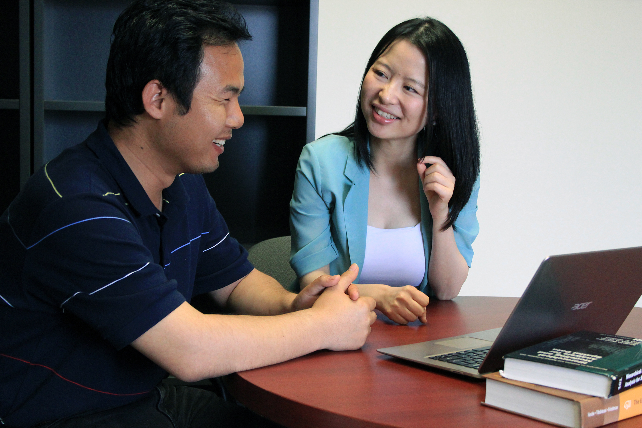 Dr. Huiyan Sang sits at a table with a graduate student and looks at a laptop