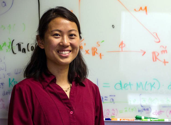 Texas A&M mathematician Annie Shiu poses for the camera in front of a whiteboard