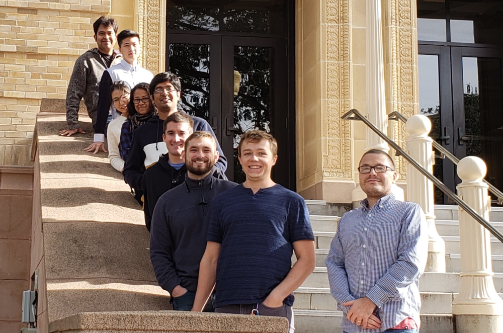 Chemist Jonathan Sczepanski poses with his research group on the steps of the Chemistry Building
