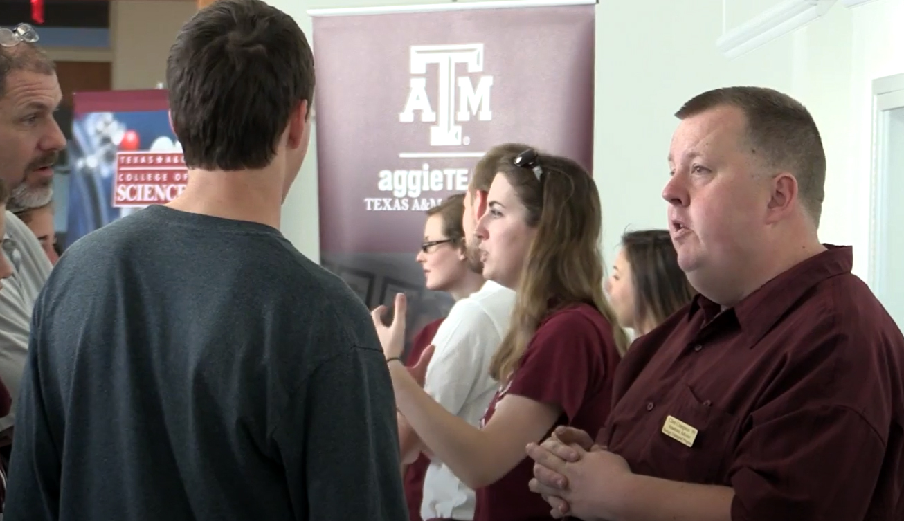 Texas A&M biology academic advisor Clint Crampton visits with prospective undergraduate students and their families at Aggieland Saturday