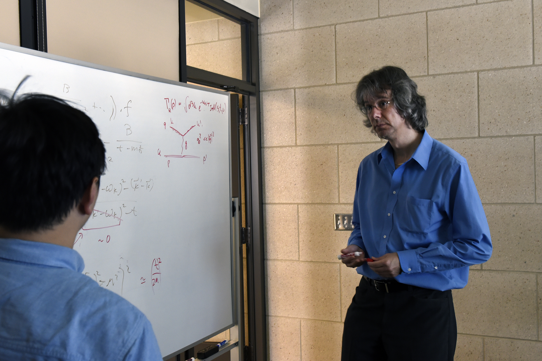 Texas A&M physicist Ralf Rapp discusses a research project with a member of his group