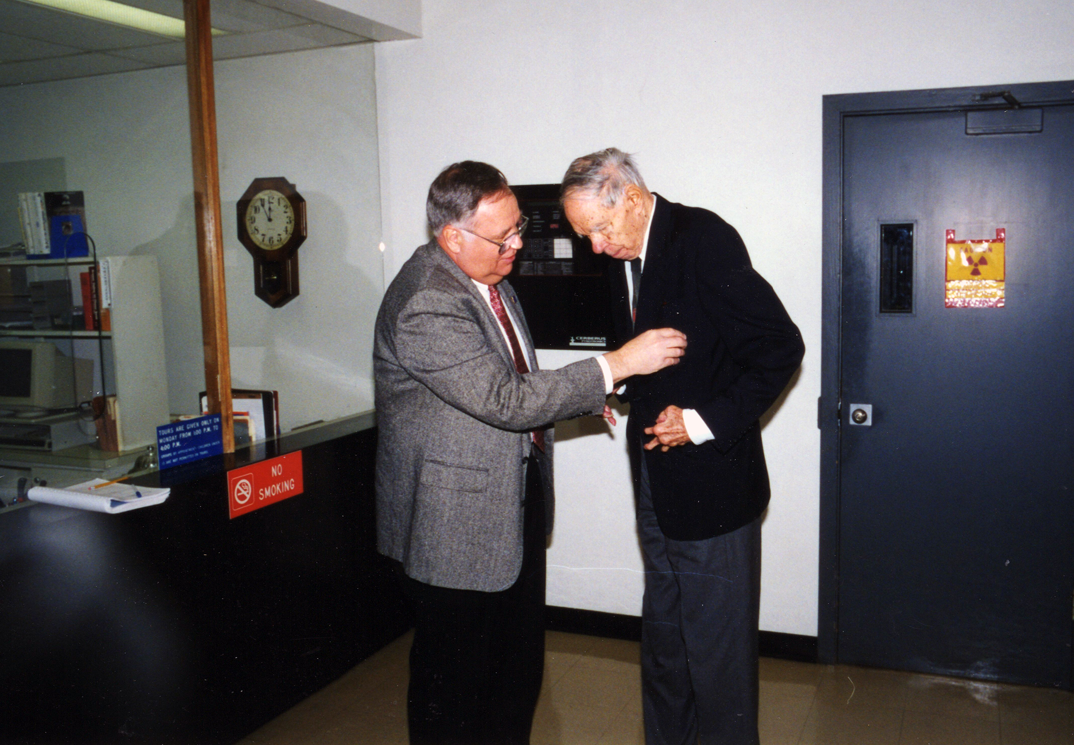 Texas A&M Distinguished Professor of Chemistry and Former Cyclotron Institute Director Joseph B. Natowitz helps 1951 Nobel Prize in Chemistry recipient Glenn T. Seaborg affix his dosimeter prior to embarking on a Cyclotron Institute tour during his March 1998 visit to Texas A&M University