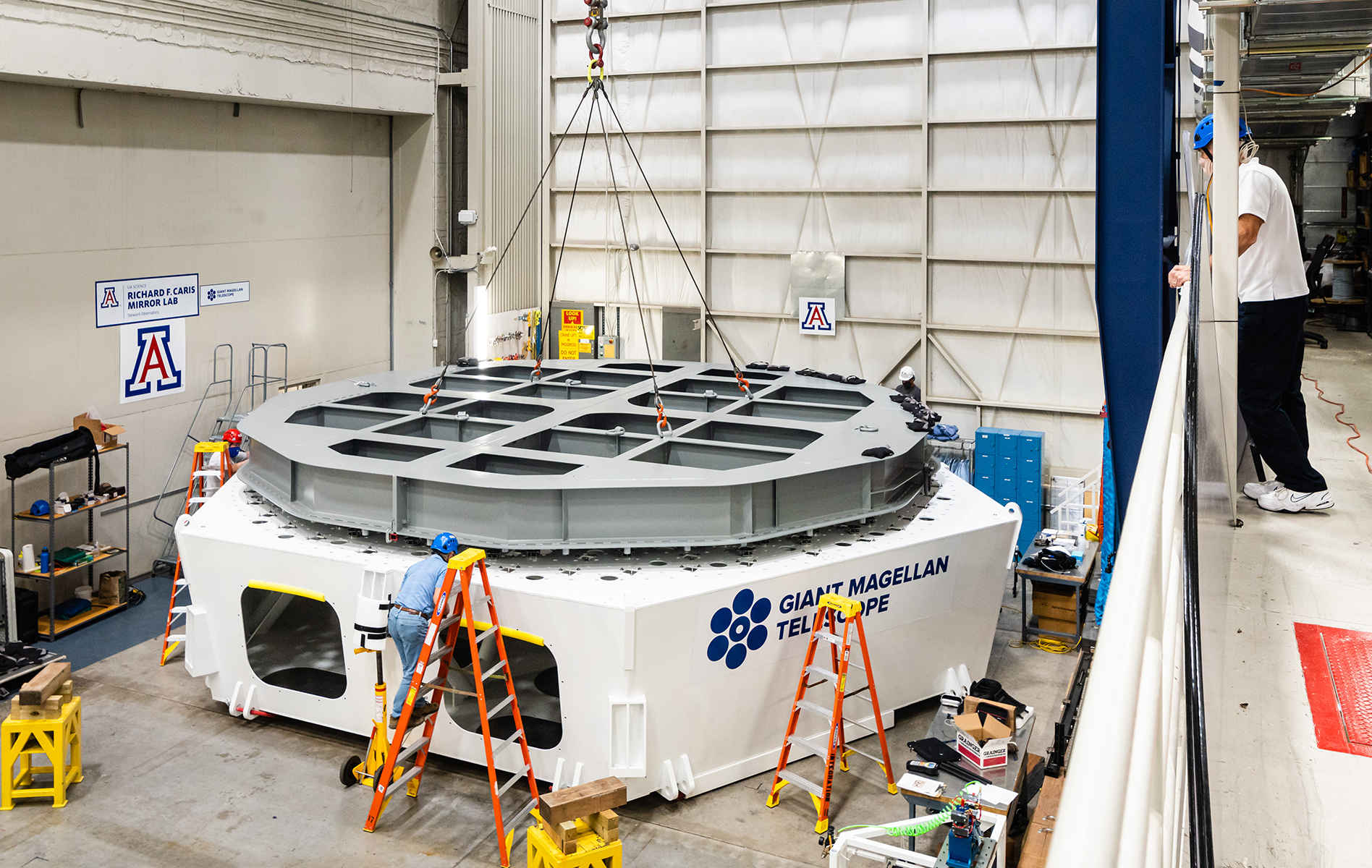 A gray steel structure that simulates one of the massive 16.5-ton Giant Magellan Telescope primary mirror segments is installed onto a test cell in the Richard F. Caris Mirror Lab at the University of Arizona. The GMT test cell and mirror simulator will be used to test the support structure and actuators being built, tested and assembled at Texas A&M University to hold the massive telescope in place, including the software that controls the precise movements of the mirrors