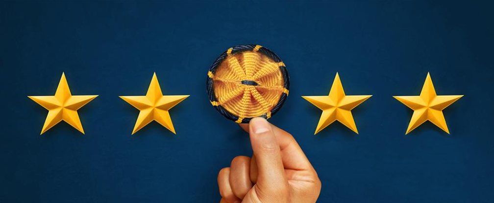 Four gold stars against a blue background featuring a hand holding the gold and blue American Association for the Advancement of Science rosette pin representing science and engineering, respectively