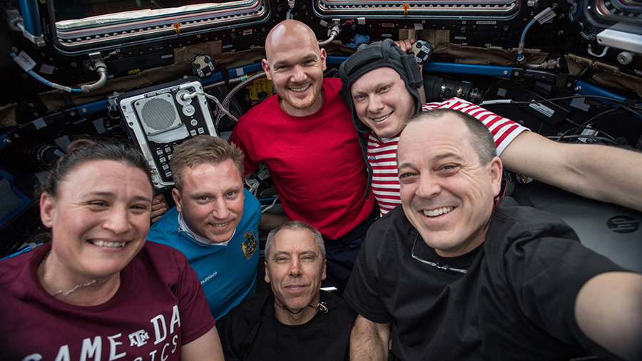 NASA astronaut Serena Auñón-Chancellor (left), wearing a Game Day Physics t-shirt onboard the International Space Station