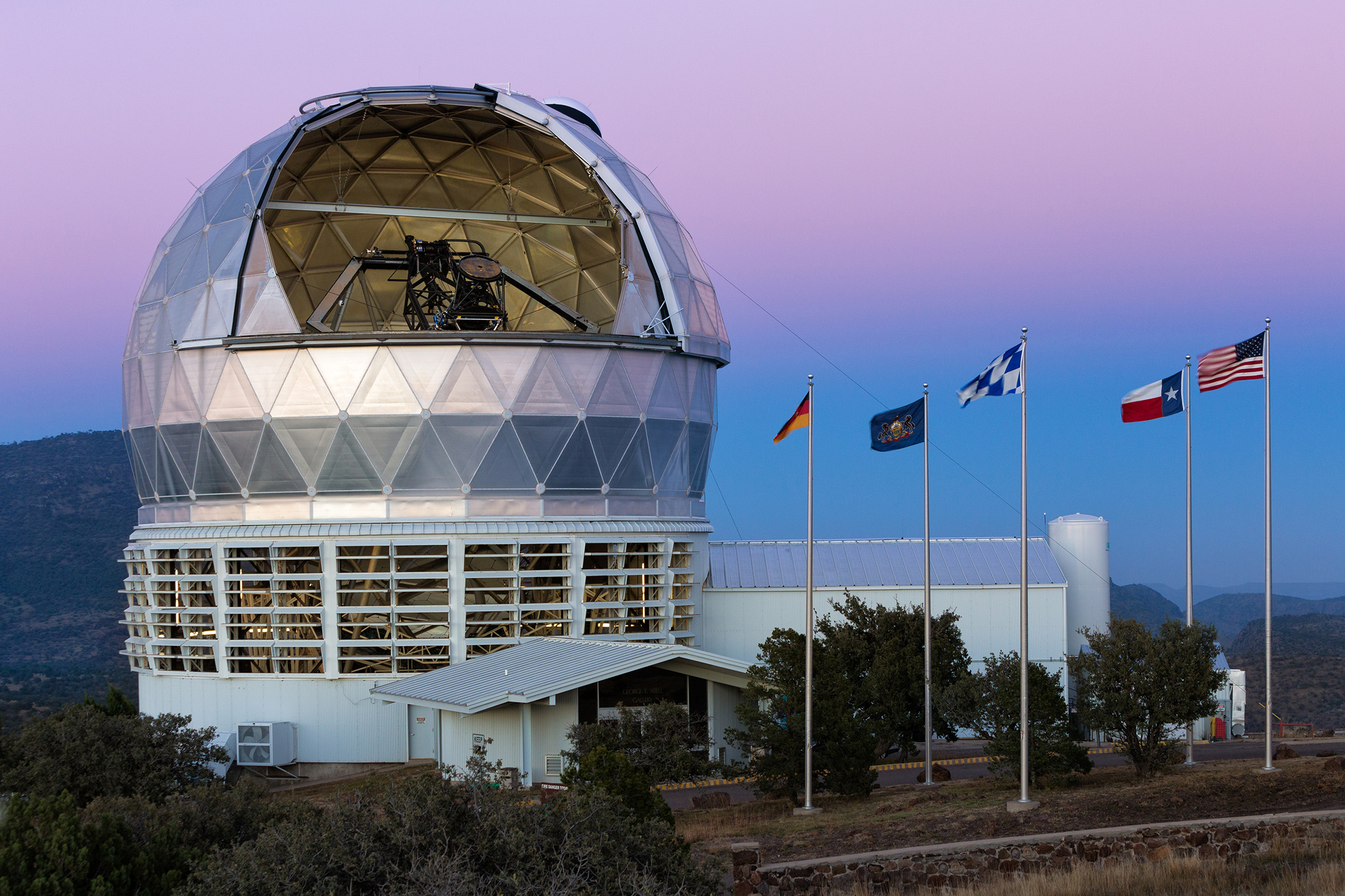 Hobby-Eberly Telescope at dusk with the flags of the four partner institutions flying alongside the U.S. flag outside the open dome